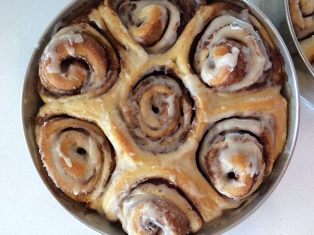 close-up of cinnamon rolls with icing in a pan