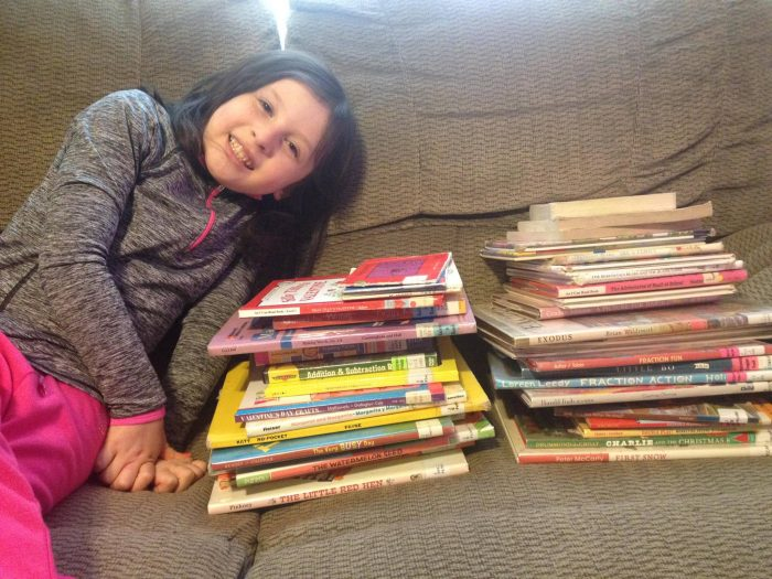 child with stacks of books