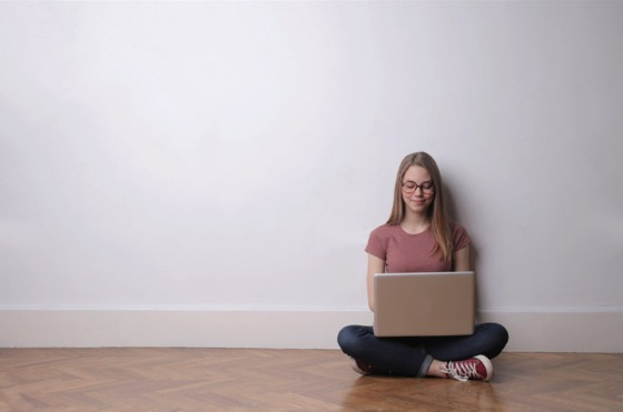 Girl on Computer in Empty Room