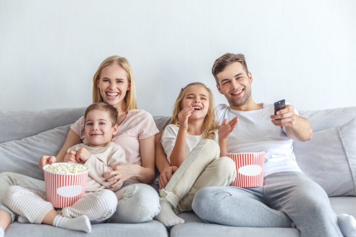 family having a movie night on the couch with popcorn