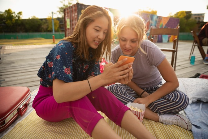 Teenage girls using smart phone in sunny urban park